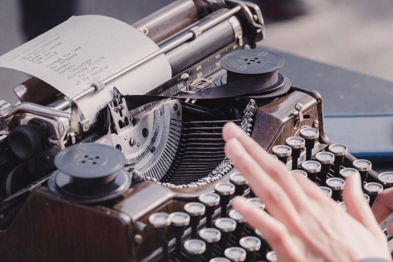 a person typing lyrics on a typewriter