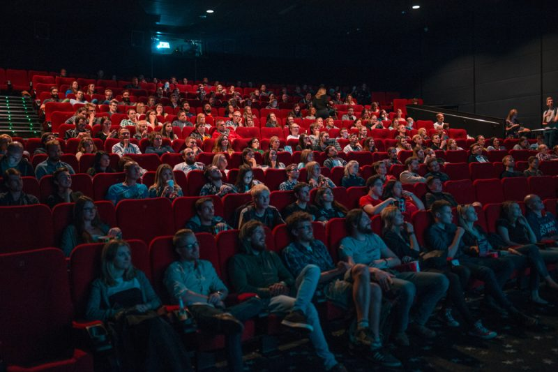 people sitting in a theater watching a film that could include your licensed music